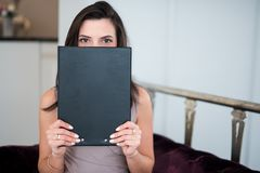看在纸上的美丽的年轻女人在掩藏她的面孔的她的手上 免版税库存照片