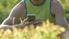 看在绿草的年轻逗人喜爱的人智能手机反对美好的自然背景在夏天 股票视频
