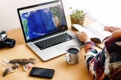 看在膝上型计算机和举行的时髦的女孩行家地图 免版税库存图片