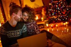 看在膝上型计算机的年轻夫妇 免版税库存图片
