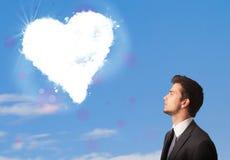 看在蓝天的英俊的人白色心脏云彩 免版税库存图片
