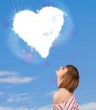 看在蓝天的逗人喜爱的女孩白色心脏云彩 图库摄影
