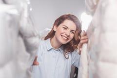 看在衣物之间的微笑的女性干洗工作者照相机在塑料袋垂悬 免版税库存照片