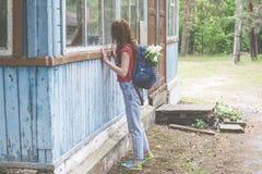看在被放弃的房子的窗口的年轻美丽的女孩 免版税图库摄影