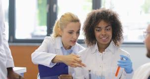看在试管的小组科学家化学制品做关于在现代的实验的笔记 股票视频