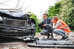 看在路的保险代理公司和妇女司机汽车在事故以后 库存图片