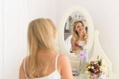 看在镜子刷子头发,女孩早晨愉快微笑的美丽的白肤金发的妇女 免版税图库摄影