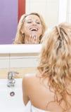 看在镜子和审查她的面孔的正面和微笑的白种人白肤金发的妇女 免版税库存照片