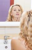 看在镜子和审查她的面孔的肉欲的白种人白肤金发的妇女 免版税库存照片