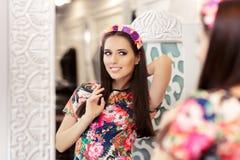 看在镜子和尝试在花服的美丽的女孩 免版税库存图片