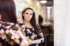 看在镜子和尝试在花服的美丽的女孩 图库摄影