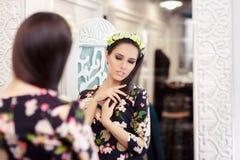 看在镜子和尝试在花服的美丽的女孩 免版税库存照片