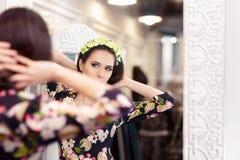 看在镜子和尝试在花服的美丽的女孩 免版税图库摄影