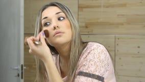 看在镜子和应用与一把大刷子的女孩化妆用品 股票录像