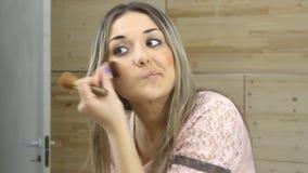 看在镜子和应用化妆用品的美丽的女孩 影视素材