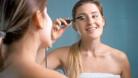 看在镜子和应用染睫毛油的美丽的微笑的妇女画象  免版税库存图片