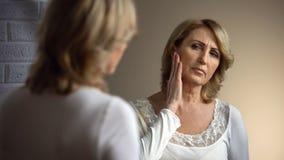 看在镜子的沮丧的年长妇女,接触起皱纹的面孔,失去的秀丽 免版税库存照片