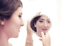 看在镜子的端庄的妇女 库存照片