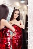 看在镜子的红色衣服饰物之小金属片礼服的美丽的女孩 库存图片