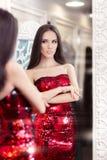 看在镜子的红色衣服饰物之小金属片礼服的美丽的女孩 图库摄影