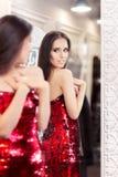 看在镜子的红色衣服饰物之小金属片礼服的美丽的女孩 免版税库存照片