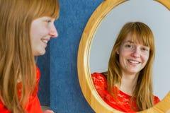 看在镜子的红头发人女孩画象 图库摄影