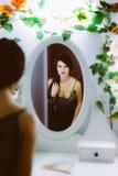 看在镜子的美丽的少妇 图库摄影