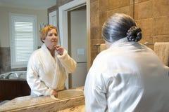 看在镜子的老妇人更加年轻的反射 免版税库存图片