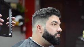 看在镜子的英俊的有胡子的人在理发以后 在理发店 影视素材