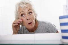 看在镜子的资深夫妇妇女反射为老化的标志 免版税库存图片