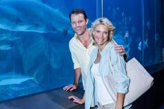 看在鱼缸旁边的愉快的夫妇照相机 图库摄影