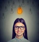 看在头上的明亮的电灯泡的玻璃的激动的妇女有一个想法 免版税库存图片