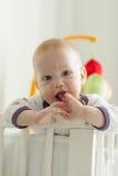 看在他的床外面的快乐的婴孩 库存图片