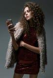 看在他的电话的少妇,在演播室 库存图片