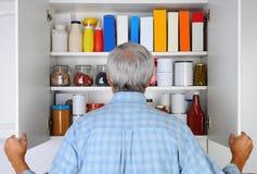 看在他的餐具室的人 免版税库存图片
