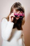 看在滑稽的桃红色玻璃的年轻美丽的妇女 免版税库存图片