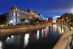看在Dambovita河的日落的布加勒斯特法院大楼 免版税图库摄影