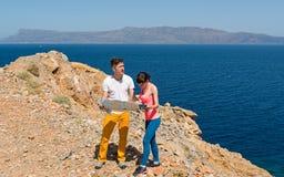 看地图的一对年轻夫妇在海附近 库存照片