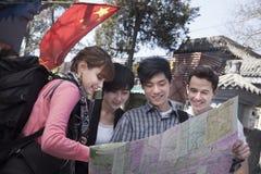 看地图的四青年人。 免版税图库摄影