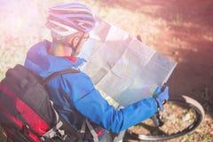 看地图的大角度观点的男性山骑自行车的人 免版税图库摄影