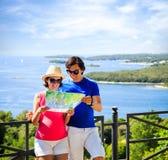 看地图的夫妇由海 免版税库存图片