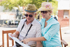 看地图的愉快的旅游夫妇在城市 免版税库存图片