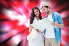 看地图的愉快的行家夫妇的综合图象 免版税图库摄影