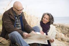 看地图的成熟夫妇 免版税库存图片
