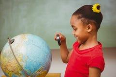 看地球的女孩通过放大镜 免版税库存图片
