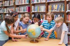 看地球的逗人喜爱的学生在图书馆里 库存图片