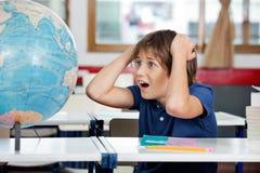 看地球的震惊男小学生在教室 库存照片