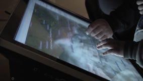 看地球,手特写镜头的地图在屏幕知觉交互式桌上的孩子和人 股票录像