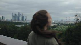 看城市的后面观点的一个美丽的女孩 都市风景 女孩让她的棕色长的头发下来 股票视频