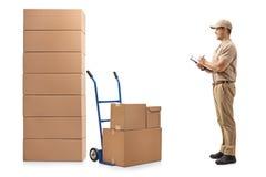 看堆箱子和写在clipbo的送货人 免版税库存图片
